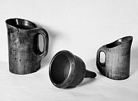 0094573 © Granger - Historical Picture ArchiveCOLONIAL UTENSILS.   Hand carved mugs and funnel. 20th century photograph.