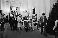 0131180 © Granger - Historical Picture ArchiveWHITE HOUSE: SANTA CLAUS.   First Lady Betty Ford with Santa Claus, and clowns leading a procession of Diplomatic Corps children at a the White House Christmas party, Washington, D.C. Photograph, 6 December 1975.