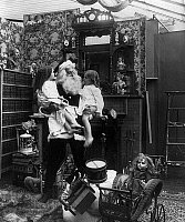 0131183 © Granger - Historical Picture ArchiveCHRISTMAS EVE, c1906.   A studio photograph of Santa Claus holding two little girls. Stereograph, c1906.