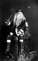 0131187 © Granger - Historical Picture ArchiveCHRISTMAS EVE, c1900.   A studio portrait of a man dressed as Santa Claus seated on a chimney while smoking a long pipe and blowing circles of smoke. Photograph, c1900.