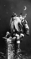 0131188 © Granger - Historical Picture ArchiveCHRISTMAS EVE, c1900.   A studio portrait of a man dressed as Santa Claus seated on a chimney. Photograph, c1900.
