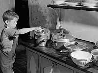 0123256 © Granger - Historical Picture ArchiveTHANKSGIVING, 1940.   A young boy inspects a pot of pudding cooking on the stove for Thanksgiving dinner, at his home in Ledyard, Connecticut. Photograph by Jack Delano, November 1940.