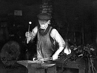 0120055 © Granger - Historical Picture ArchiveBLACKSMITH, c1910.   An American blacksmith at work in a shop. Photograph, c1910.