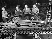 0117459 © Granger - Historical Picture ArchiveTRACTOR BELT FACTORY, 1941.   Factory crew at the White Motor Company in Cleveland, Ohio, mounting a tractor belt on a half-track military vehicle for the U.S. Army during World War II. Photograph by Alfred Palmer, December 1941.