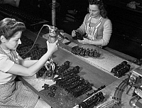 0117986 © Granger - Historical Picture ArchiveTOY FACTORY, 1942.   Factory workers Stephanie Cewe (left) and Ann Manemeit at work at a toy factory in New Haven, Connecticut. Stephanie assembles toy trains while Ann attaches the trains to their chassis. The factory was later converted to manufacture parachute flare casings during World War II. Photograph by Howard R. Hollem, 1942.