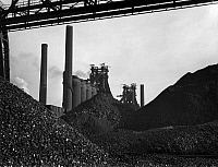 0108616 © Granger - Historical Picture ArchiveSTEEL FACTORY, 1941.   Piles of iron ore in front of the blast furnaces at the Carnegie-Illinois Steel Corporation in Farrell, Pennsylvania. Photograph by Alfred Palmer, November 1941.