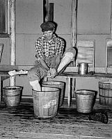 0118582 © Granger - Historical Picture ArchiveMINNESOTA: LUMBER CAMP, 1937.   A lumberjack washing his feet in a lumber camp, near Effie, Minnesota. Photograph by Russell Lee, September 1937.