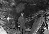 0107786 © Granger - Historical Picture ArchiveHINE: COAL MINER, 1908.   A miner in front of a great fall of slate that blocked the entry to Turkey Knob Mine, Macdonald, West Virginia. Photograph by Lewis Hine, October 1908.
