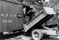 0121934 © Granger - Historical Picture ArchiveFREIGHT CAR, 1940.   Workers loading gold ore concentrate into a freight car of a narrow gauge railroad, Ouray, Colorado. Photograph by Russell Lee, September 1940.