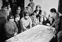 0168543 © Granger - Historical Picture ArchiveINDUSTRY: OIL REFINERY.   Men studying an oil flow chart showing the course of oil through a refinery, using the process of 'cracking,' to supply fuel for American combat units fighting in World War II. Photograph, c1944.