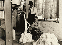 0132847 © Granger - Historical Picture ArchiveHINE: CHILD LABOR, 1908.   Boy using a warping machine with a man overseeing his work at the Catawba Cotton Mill in Newton, North Carolina. Photograph by Lewis Hine, December 1908.