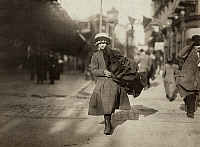 0167520 © Granger - Historical Picture ArchiveHINE: HOME INDUSTRY, 1912.   A young girl carrying a bundle of coats for home-work near Astor Place in New York City. Photograph by Lewis Hine, February 1912.
