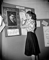 0117626 © Granger - Historical Picture ArchiveLABOR MOVEMENT, 1938.   Marian Hepburn, sister of actress Katherine Hepburn and member of the United Federal Workers of America, posts a flyer on a bulletin board near a calendar with a portrait of labor leader John L. Lewis, December 1937.