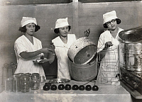 0117903 © Granger - Historical Picture ArchiveDEMONSTRATION TEAM, 1921.   Three young women demonstrate how teamwork makes for efficiency in canning farm products at the State 4-H Fair in Charleston, West Virginia. Photograph by Lewis Hine, 1921.