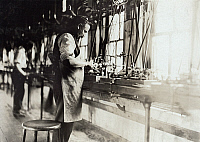 0117912 © Granger - Historical Picture ArchiveHINE: WATCH FACTORY, 1908.   A man tending to a machine that makes the tiny screws used in watches at a factory in South Bend, Indiana. Photograph by Lewis Hine, 1908.