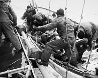 0099586 © Granger - Historical Picture ArchiveRESCUE AT SEA, 1952.   Two injured survivors from the broken tanker 'Fort Mercer' are helped onboard the U.S. Coast Guard cutter Yakutat from a motor surfboat, 18 February 1952.