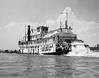 0128939 © Granger - Historical Picture ArchiveMISSISSIPPI STEAMBOAT.  Stern view of the steamer 'Misissippi' bound upstream with two barges of fuel oil. Photograph, mid-20th century.