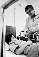 0173374 © Granger - Historical Picture ArchiveAMERICORPS VOLUNTEER, 1971.   An Americorps Foster Grandparent, Josephine Caneles, holding a doll for a young patient at Jefferson Davis Hospital in Houston, Texas. Photograph, 1971.