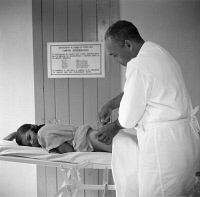 0325935 © Granger - Historical Picture ArchivePUERTO RICO: HEALTH CENTER.   A doctor administering an anti-malarial injection in a Puerto Rico Resettlement Administration health center in San Juan, Puerto Rico. Photograph by Edwin Rosskam, 1938.