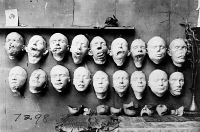 0162732 © Granger - Historical Picture ArchiveWORLD WAR I: MASKS, 1918.   Masks showing the work done by Anna Coleman Ladd of the American Red Cross. The top row are casts taken from soldiers' mutilated faces, the bottom row shows masks of their faces before their injuries, made from pre-war photographs. On the table are masks made to fit over the disfigured part of the face. Photograph, 1918.