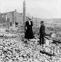 0119413 © Granger - Historical Picture ArchiveSAN FRANCISCO EARTHQUAKE.   A man and woman standing amid the rubble, following the earthquake of 18 April 1906. Stereograph, 1906.