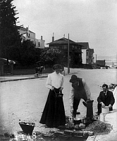 0119583 © Granger - Historical Picture ArchiveSAN FRANCISCO EARTHQUAKE.   A woman and two men cooking on a fire next to the curb of a residential street, following the earthquake of 18 April 1906. Stereograph, 1906.
