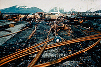 0185860 © Granger - Historical Picture ArchiveALASKA: EARTHQUAKE, 1964.   The railroad facilities at Seward Port in Alaska, which was damaged by the main tsunami caused by the earthquake of 27 March 1964. The rails were stripped from the ties by the waves, and the oil storage tanks were damaged by fire. Photograph, 1964.