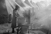 0325228 © Granger - Historical Picture ArchiveARKANSAS: REFUGEES, 1937.   A flood refugee washing clothes in the refugee camp at Forrest City, Arkansas, after the Ohio River flood. Photograph by Edwin Locke, February 1937.