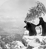 0129243 © Granger - Historical Picture ArchiveGRAND CANYON: SIGHTSEERS.   One woman holding another by the coat near the edge of a snow-covered cliff overlooking the Grand Canyon in Arizona. Stereograph, c1925.