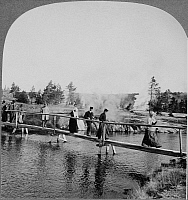0129737 © Granger - Historical Picture ArchiveYELLOWSTONE: TOURISTS, c1904.   Tourists walking across a footbridge among the geysers in Yellowstone National Park, Wyoming. Stereograph, c1904.