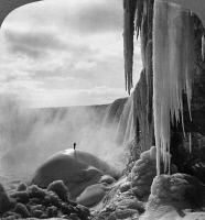 0113451 © Granger - Historical Picture ArchiveNIAGARA FALLS: FROZEN.  Person standing on top of ice mound at Niagara Falls in winter, stereograph by R.Y. Young, c1903.