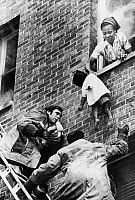 0129619 © Granger - Historical Picture ArchiveCHILDREN RESCUED, 1976.   Marie Ateba hands her children to firemen on a ladder after a fire broke out in her apartment in Washington, D.C., 1976.