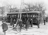 0409639 © Granger - Historical Picture ArchiveFIREMEN, c1918.   Firemen with hoses over a street car, United States. Photograph, c1918.