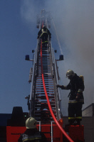 0621194 © Granger - Historical Picture ArchiveFIREFIGHTING, 1993.   Firefighters ascending a ladder to combat a blaze in Witten, Germany. Photograph by Markus Matzel, 10 April 1993. Full Credit: ullstein bild - Markus Matzel / Granger, NYC. All Rights Reserved.