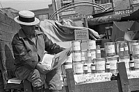 0121772 © Granger - Historical Picture ArchiveTEXAS: HONEY VENDOR, 1939.   Honey peddler reading a newspaper in a farmer's market in San Antonio, Texas. Photograph by Russell Lee, March 1939.