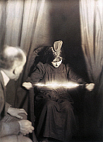 0118600 © Granger - Historical Picture ArchiveMEDIUM DURING SÉANCE, 1912.   'The medium Eva C. with a materialization on her head and a luminous apparition between her hands.' Manipulated photograph taken during a séance, by German photographer Albert von Schrenk-Notzing, 17 May 1912.