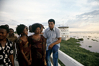 0167448 © Granger - Historical Picture ArchiveMUHAMMAD ALI (1942-2016).   Né Cassius Clay. American heavyweight boxer with members of his entourage on the shore of the Congo River at Kinshasa, Zaire, September 1974, prior to his championship fight agasint George Foreman. The hospital ship 'Mama Mobutu' is moored in the background at right.
