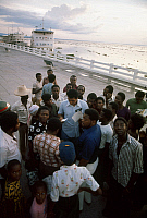 0167449 © Granger - Historical Picture ArchiveMUHAMMAD ALI (1942-2016).   Né Cassius Clay. American heavyweight boxer. Signing an autograph amidst a crowd of admirers on the shore of the Congo River at Kinshasa, Zaire, September 1974, prior to his championship fight agasint George Foreman. The hospital ship 'Mama Mobutu' and the presidential yacht 'President Mobutu' are moored in the background at left.