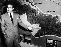 0040635 © Granger - Historical Picture ArchiveFULGENCIO BATISTA (1901-1973).   Cuban soldier and dictator. Standing at a relief map of Cuba, Batista explains how government troops have isolated and contained the rebel forces of Fidel Castro, April 1958.