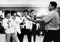 0115147 © Granger - Historical Picture ArchiveBEATLES AND CLAY, 1964.   The Beatles (from left: Ringo Starr, John Lennon, George Harrison, and Paul McCartney) clowning with boxer Cassius Clay (later Muhammad Ali) at his training camp in Miami Beach, Florida, 18 February 1964, one week prior to his heavyweight championship fight with Sonny Liston.