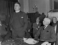 0018417 © Granger - Historical Picture ArchiveCHARLES EDWARD COUGHLIN (1891-1979). American (Canadian-born) Roman Catholic priest. Coughlin testifying at the National Monetary Conference in Washington, D.C., January 1935. Seated, to the right, is Senator Elmer Thomas of Oklahoma.