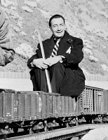 0623282 © Granger - Historical Picture ArchiveSALVADOR DALI (1904-1989).   Spanish painter. Dali seated on a coal car of Walt Disney's scale model steam railroad, the Carolwood Pacific Railway, in the backyard of Disney's house in Los Angeles, California. Photograph by Earl Theisen, c1951.