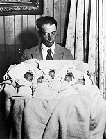 0013417 © Granger - Historical Picture ArchiveDIONNE QUINTUPLETS, 1934.   Oliva Dionne with his quintuplet daughters shortly after their birth on 28 May 1934 at Callendar, Ontario, Canada.