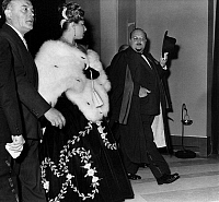 0169993 © Granger - Historical Picture ArchiveFAROUK I (1920-1965).   King of Egypt, 1936-1952. The exiled former king doffing his hat to his longtime companion, the Italian opera singer Irma Capece Minutolo (1935- ), while leaving the premiere of the film 'War and Peace' at the Teatro dell'Opera in Rome, Italy, October 1956.