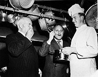 0170511 © Granger - Historical Picture ArchiveDUNCAN HINES (1880-1959).   American food critic and author. Hines (left) and Ted Shane sampling food prepared by Francis Chevalier (right) at the 2nd annual chef's tournament in Fredericksburg, Virginia, 30 March 1948.