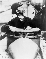 0621735 © Granger - Historical Picture ArchiveJOHN PHILIP HOLLAND   (1841-1914). Irish engineer and developer of the first submarine to be commissioned by the U.S. Navy. Holland climbing out of the hatch of the submarine. Photograph, c1910.