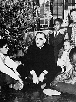 0042769 © Granger - Historical Picture ArchiveEDWARD FLANAGAN (1887-1948).   American (Irish-born) clergyman. Father Flanagan celebrating Christmas with residents of Boystown, Nebraska.