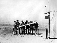 0176033 © Granger - Historical Picture ArchiveROBERT HUTCHINGS GODDARD   (1882-1945). American physicist. Second from right, with assistants holding the rocket used in the test flight on 27 October, 1931, at Roswell, New Mexico. Photograph, 1931.