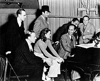 0027184 © Granger - Historical Picture ArchiveGEORGE GERSHWIN   (1898-1937). American composer. George Gershwin at the piano with, seated, Fred Astaire and Ginger Rogers. Standing, left to right, Hermes Pan, Mark Sandrich, Ira Gershwin and Nathaniel Shilkret on the film set of 'Shall We Dance.' Photograph, 1936 or 1937.