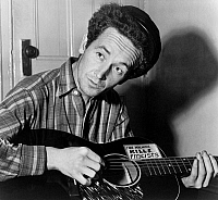 0109470 © Granger - Historical Picture ArchiveWOODY GUTHRIE (1912-1967).   American folk singer. Photographed playing a guitar that has a sticker attached reading: 'This Machine Kills Fascists.' Photograph by Al Aumuller, 8 March 1943.